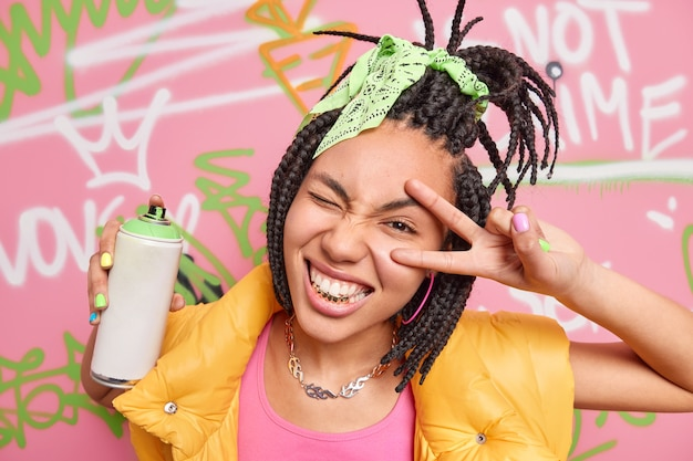 Cheerful teen girl with dreadlocks golden teeth makes peace or victory gesture makes graffiti with aerosol spray dressed in fashionable clothes