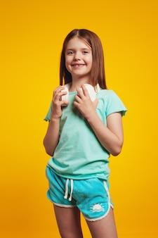 Веселая девочка-подросток с летней одеждой и белыми наушниками на шее
