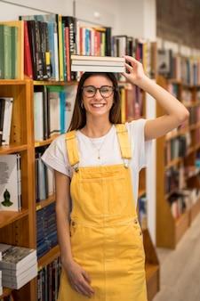 Cheerful teen schoolgirl holding books on head