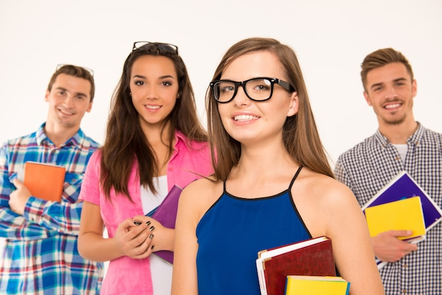 Веселые студенты-подростки держат книги и материалы