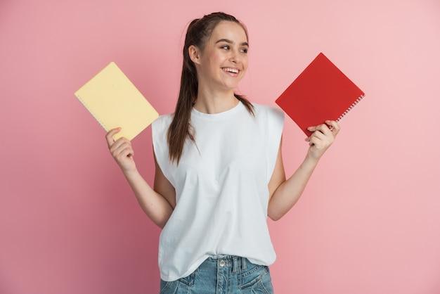 Веселая женщина-подросток улыбается и показывает ноутбуки на камеру, делая домашнее задание на розовом фоне. d.