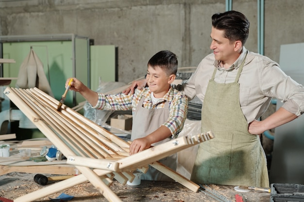 Cheerful teenage boy in apron enjoying varnishing process under control of father in workshop