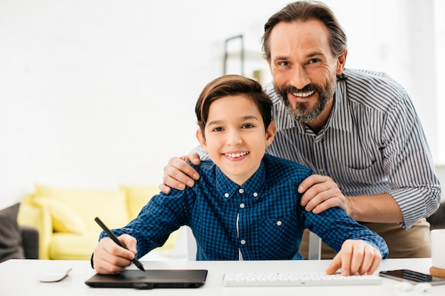 片手にスタイラスを持ってテーブルに座って、前向きな父親が背中の後ろに立っている間笑顔で陽気な10代の少年