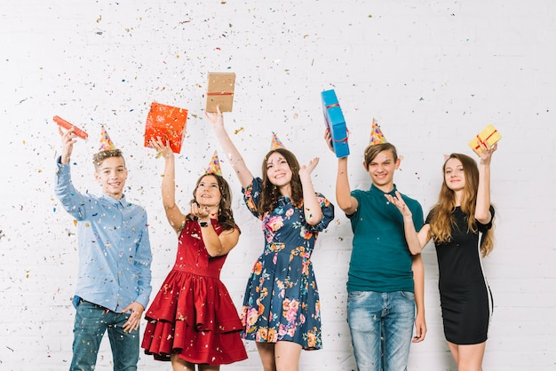 Cheerful teenage friends showered with throwing confetti on birthday party