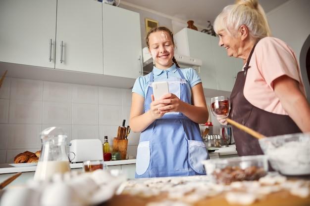 쾌활한 10대 소녀와 부엌에서 놀고 있는 사랑스러운 할머니