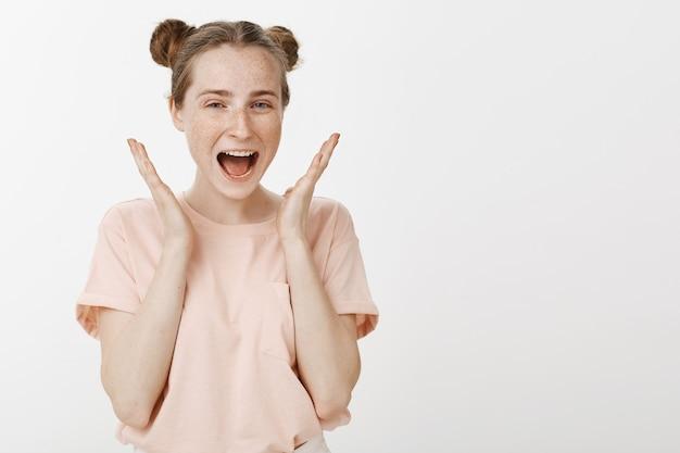 白い壁に向かってポーズをとって陽気な10代の少女