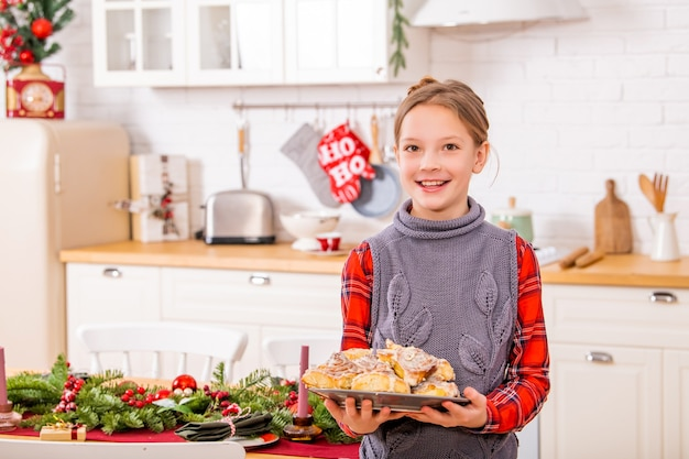 Cheerful teenage girl stands near festive christmas table and holds a dish with sweet buns in her hands.