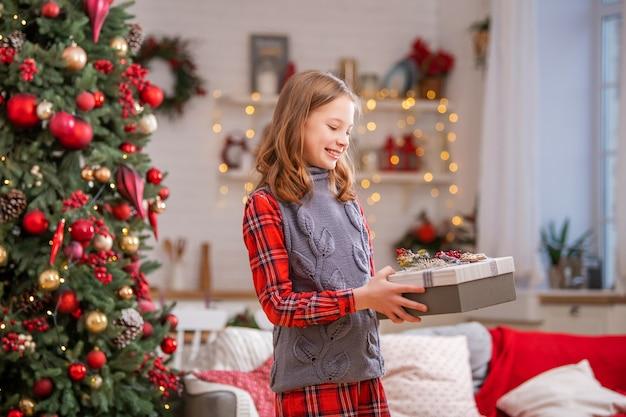 クリスマスツリーの背景に自宅で彼女の手に贈り物を箱に入れて陽気な10代の少女