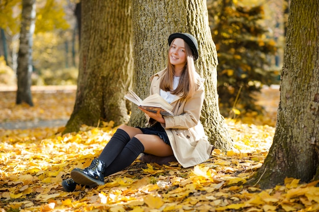 Cheerful teenage girl with a book in the forest