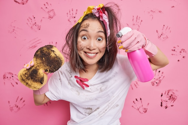 Cheerful teenage girl with pony tail smiles happily washes invisible surface with spray detergent and sponge wears white spotty t shirt has dirty face stands on pink