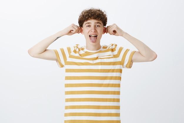 Allegro ragazzo adolescente in posa contro il muro bianco