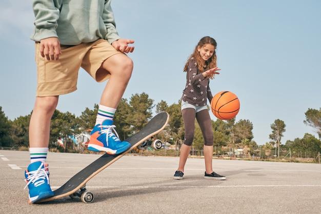 スケートボードとバスケットボールのボールをドリブルする女の子と陽気な10代のスケーター