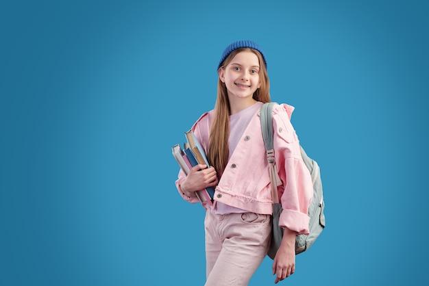 カメラの前に立っている間胸で本のスタックを保持しているピンクのデニムジャケット、ビーニーとジーンズの陽気な10代の学生