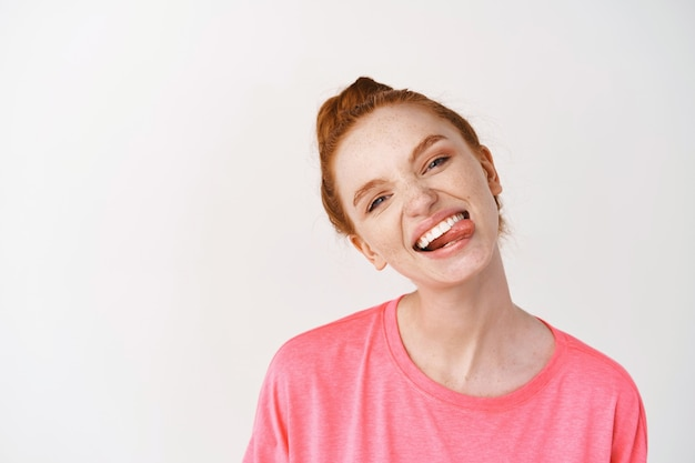 Cheerful teenage woman with ginger hair combed in messy bun, showing white smile and tongue, standing against white wall in pink t-shirt
