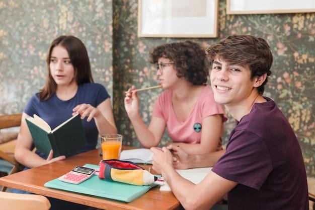 Cheerful teenager doing homework with classmates