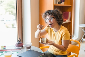 Cheerful teenager eating dessert in library