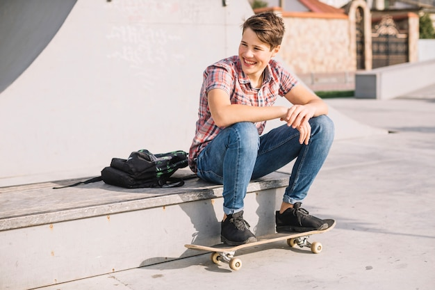 Cheerful teenager keeping feet on skateboard