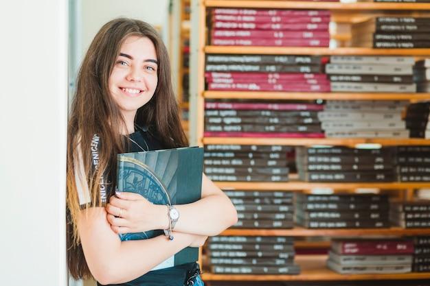 Adolescente allegro con il libro in biblioteca