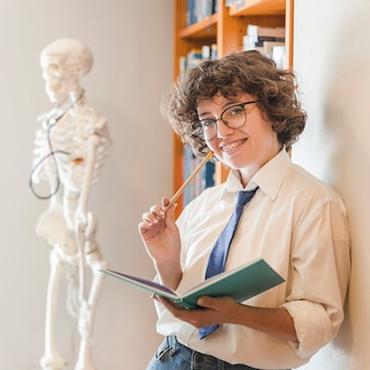 Cheerful teenager with pencil and notebook in library