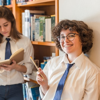 Cheerful teenager with pencil standing near friends