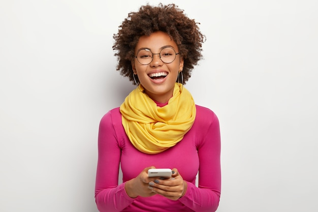 Cheerful teenager with toothy smile, afro hairstyle, holds modern cell phone, chats online with boyfriend