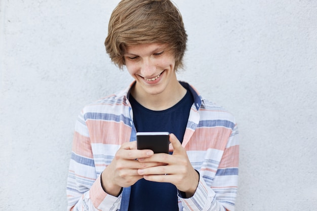 Cheerful teenager with trendy hairstyle holding modern smart phone typing messages or playing games online