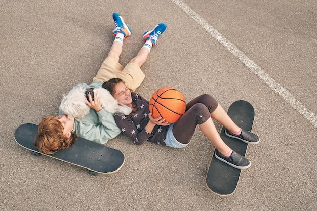 通りにスケートボードを持っている陽気なティーンエイジャー