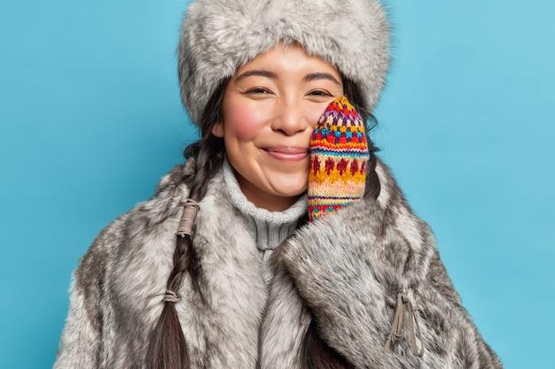 쾌활한 부드러운 에스키모 여자는 겨울 옷을 입고 뺨에 손을 유지하고 겨울철 미소는 파란색 벽에 기꺼이 포즈를 취합니다. 추운 기후