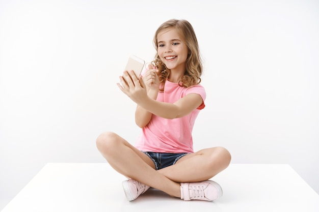 Cheerful tender glamour young blond girl talking with mom via video-call, hold smartphone pointing sideways look mobile phone at front cute, record internet blog, online stream, pose white wall
