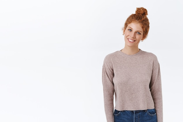 Cheerful, tender good-looking redhead caucasian woman with combed curly hairstyle, wear sweater, tilt head and smiling pleasantly, standing casual, express positive vibe, standing white wall