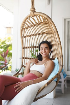 등나무 의자에 앉아 휴가를 즐기는 검은 곱슬 머리를 가진 쾌활한 부드러운 행복한 여자