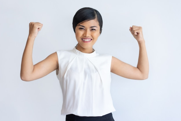 Cheerful thai girl showing strength