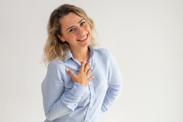 Cheerful thankful young woman honored and embarrassed