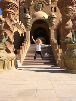 Cheerful tourist jumps near the temple