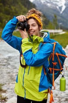 Веселый турист позирует над живописным видом, несет большой рюкзак, снимает фото на камеру, фотографирует ручей, надевает анорак.