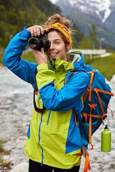 Cheerful tourist poses over scenic view, carries big backpack, shoots photo with camera, takes picture of brook, wears anorak
