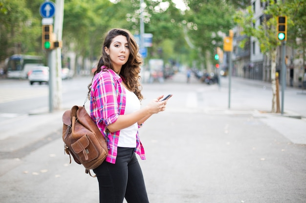 Cheerful tourist using navigation on smartphone