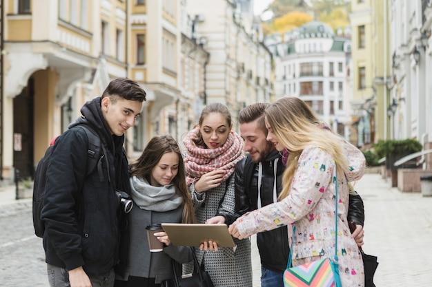 Веселые туристы с планшетом на улице
