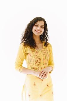 白い背景に陽気な伝統的なインドの女性。スタジオ撮影。