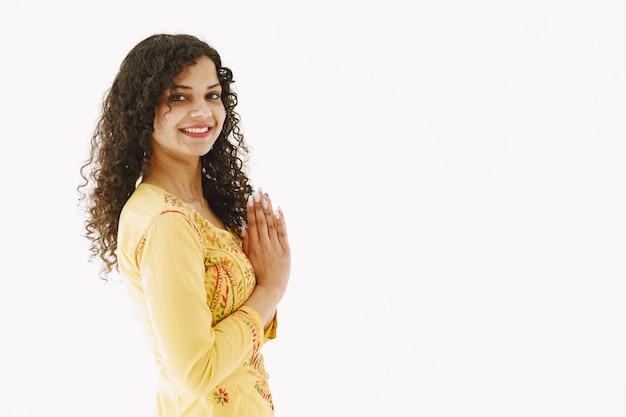 Donna indiana tradizionale allegra su priorità bassa bianca. colpo dello studio.