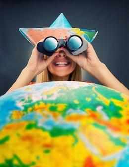Cheerful traveler girl discovering map with binoculars