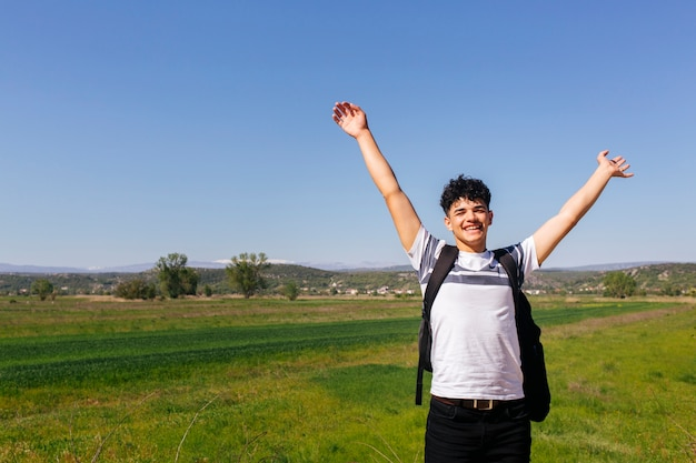 Cheerful traveler man with raised hand standing in green field