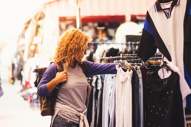 Веселый путешественник молодая блондинка кудрявая женщина ищет и выбирает одежду на рынке подержанных во время альтернативного отпуска