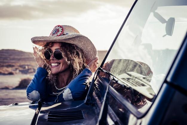 陽気なトレンディな魅力的な金髪の若い大人の女性は笑顔で冒険の田舎で車の旅を楽しんでいます-女性は屋外の車の旅の旅の間に楽しんでいます