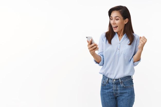 Веселая торжествующая взрослая женщина 30-х годов качает кулаком, читая отличные новости, широко улыбаясь, держа смартфон в руке, с радостью смотрите на дисплей мобильного телефона, выигрывайте онлайн-лотерею, стойте у белой стены