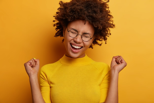 Cheerful triumphing woman achieves victory, raises clenched fists with triumph, rejoices winning prize, dressed casually, keeps eyes closed, isolated over yellow wall. celebration concept
