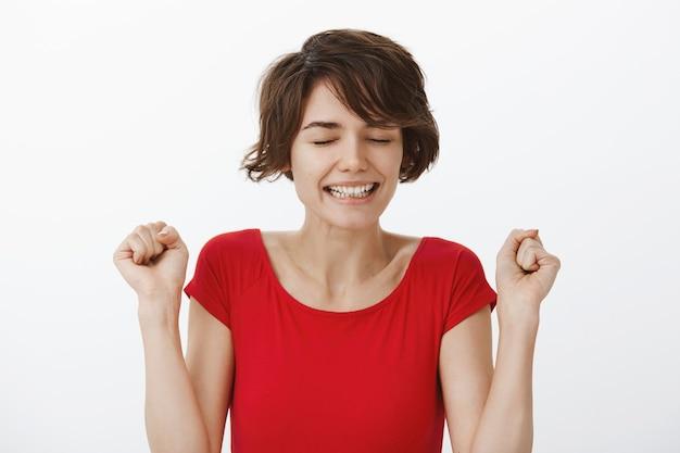 Веселая торжествующая женщина побеждает и празднует победу, танцует от радости