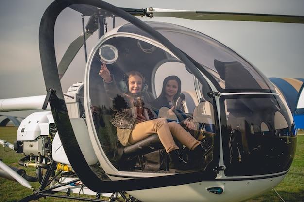 헬리콥터 조종석에서 하늘을 가리키는 쾌활한 트윈 소녀