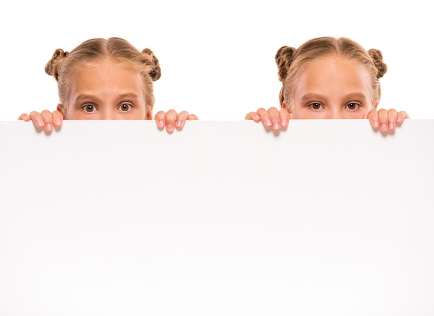 Cheerful twins girls with a white board.