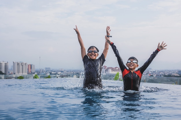 Cheerful two brothers wearing glasses raising hand together on infinity pool with city view background